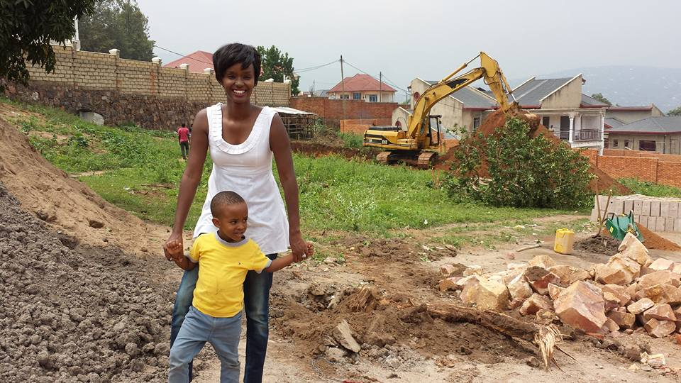Alpha Akariza, the founder of Discovery Preschool, a new preschool in the Kigali neighborhood of Gisozi, visits the school construction site with her son.