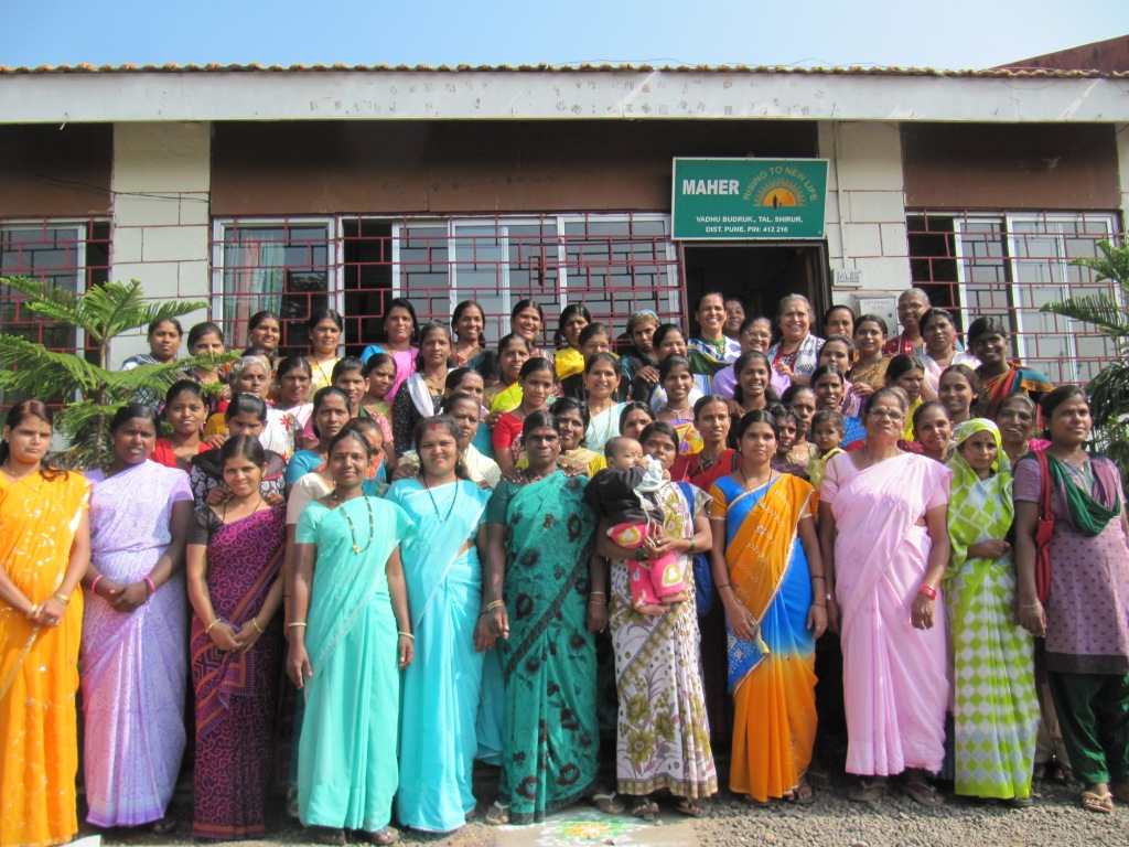 Sister Lucy and the women of Maher smiling outside the ashram.