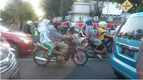 The city traffic jam: cars surrounded by crowded motorcycles.