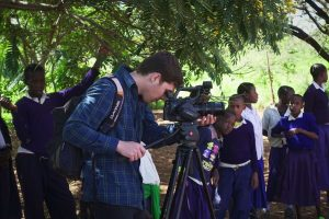 Students observe curiously while Tommy is filming at Enjoro Village Primary School, Tanzania.