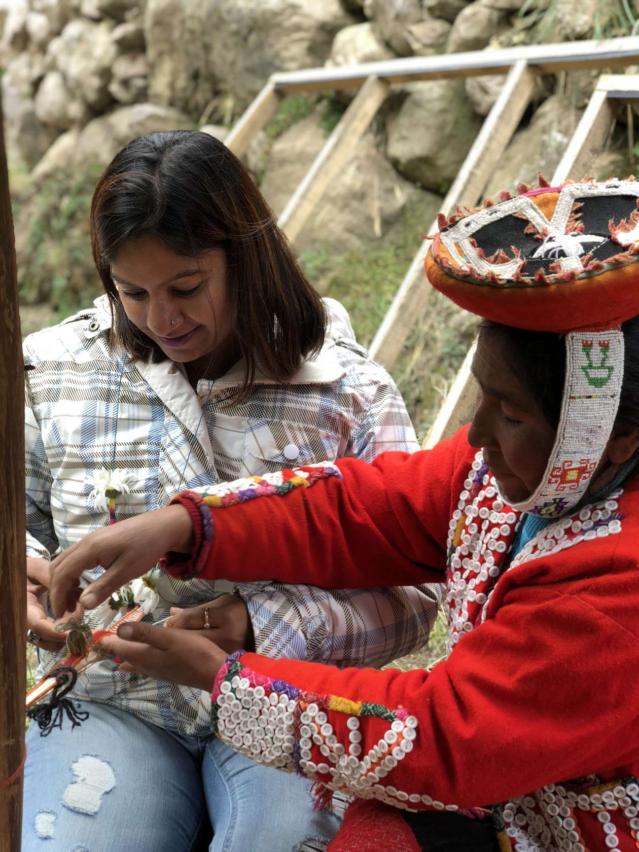 Ruchi experiencing Quechua culture learning to weave a bracelet
