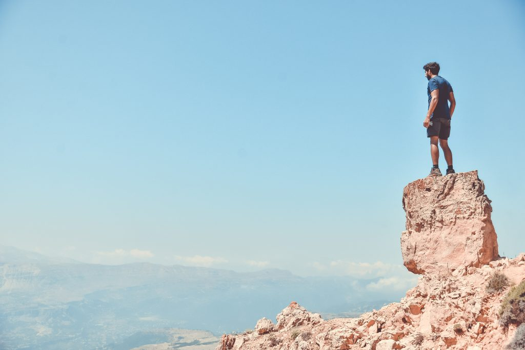 Man standing on a cliff looking off into the distance
