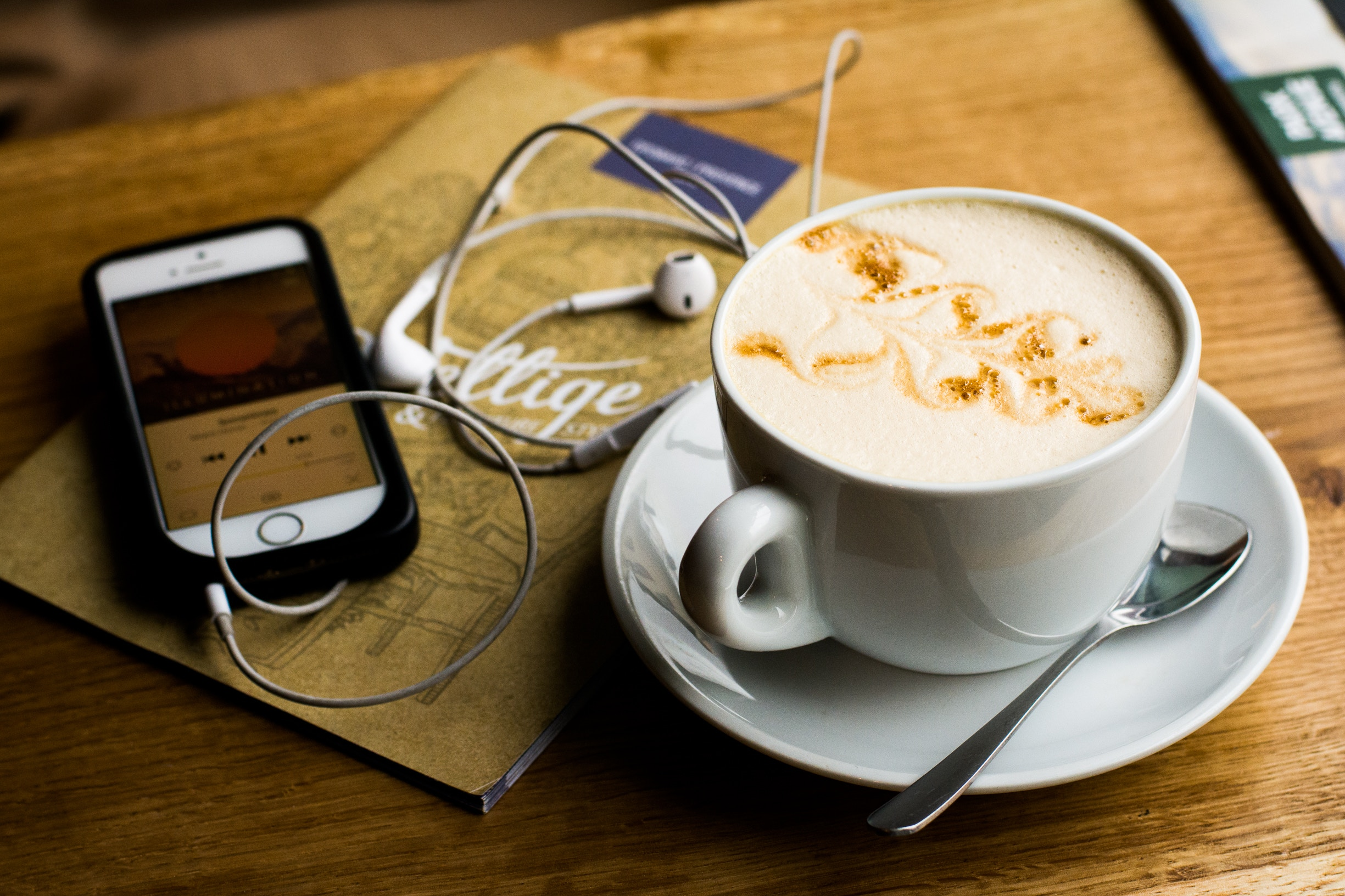flatlay of phone with headphones and cup of coffee