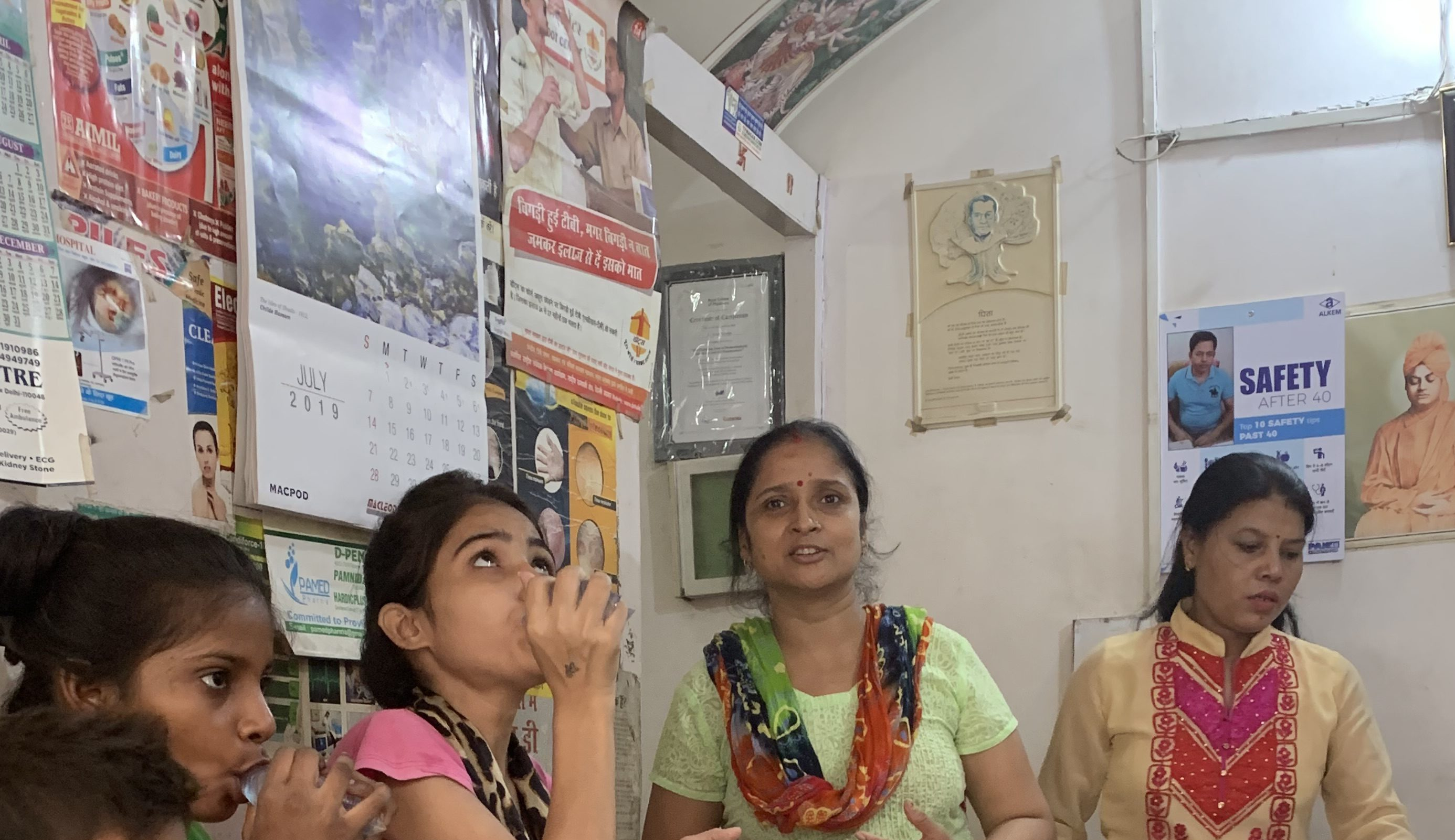 Community health workers administer TB medication to patients at a pop-up community health center in Tekhand Village India