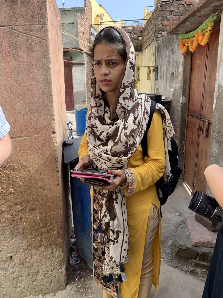 Operation ASHA team member holding a tablet in Tekhand Village and giving feedback on the mobile app