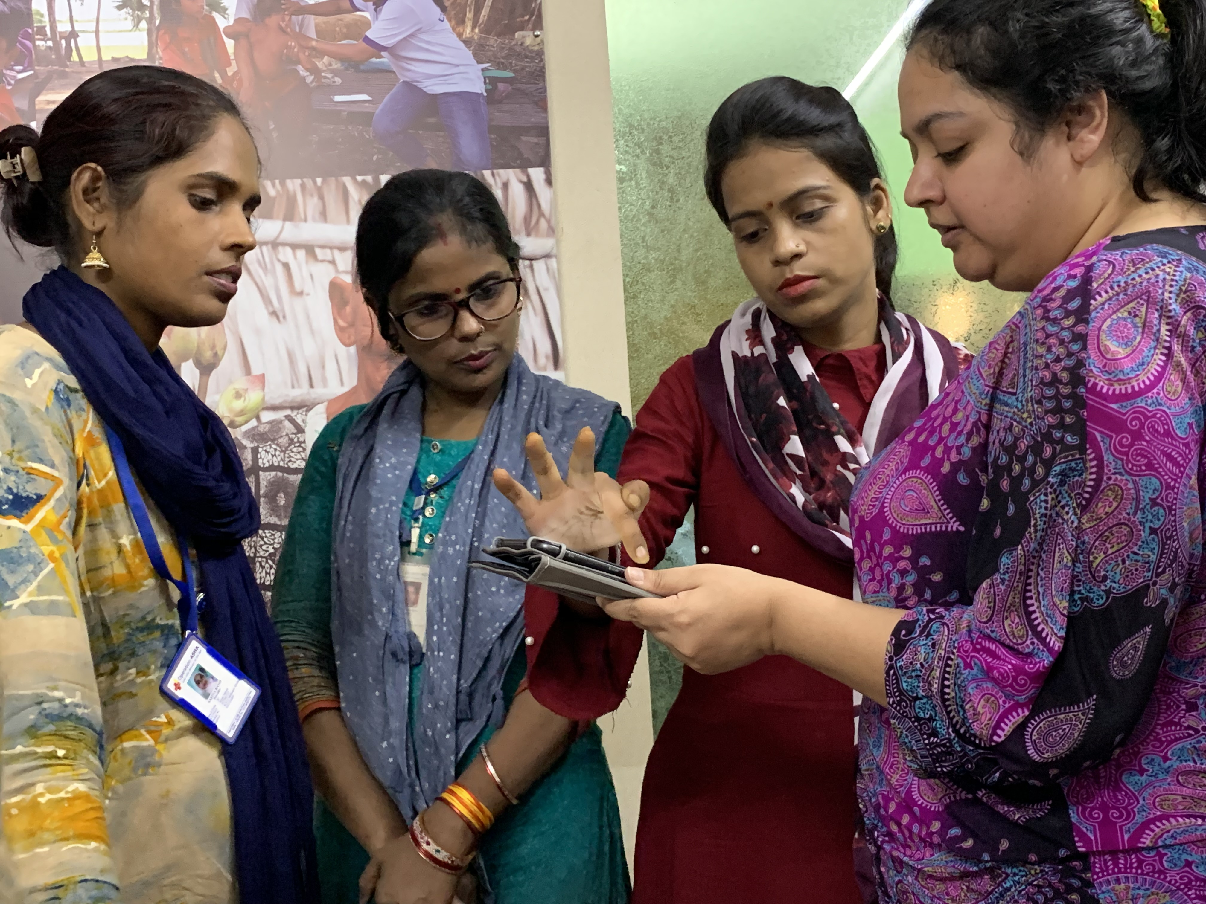 Four Operation ASHA employees looking at a tablet and pointing at and discussing different features