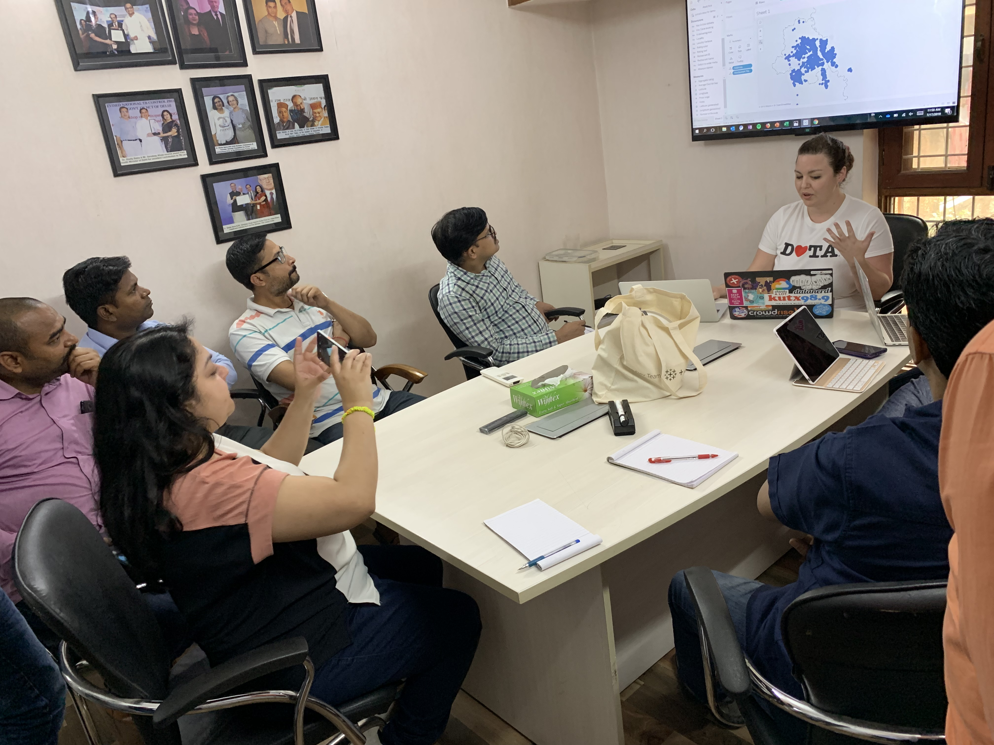 Tableau volunteer Lauren giving a demo of the Tableau software to Operation ASHA team members around a table who look on and take photos