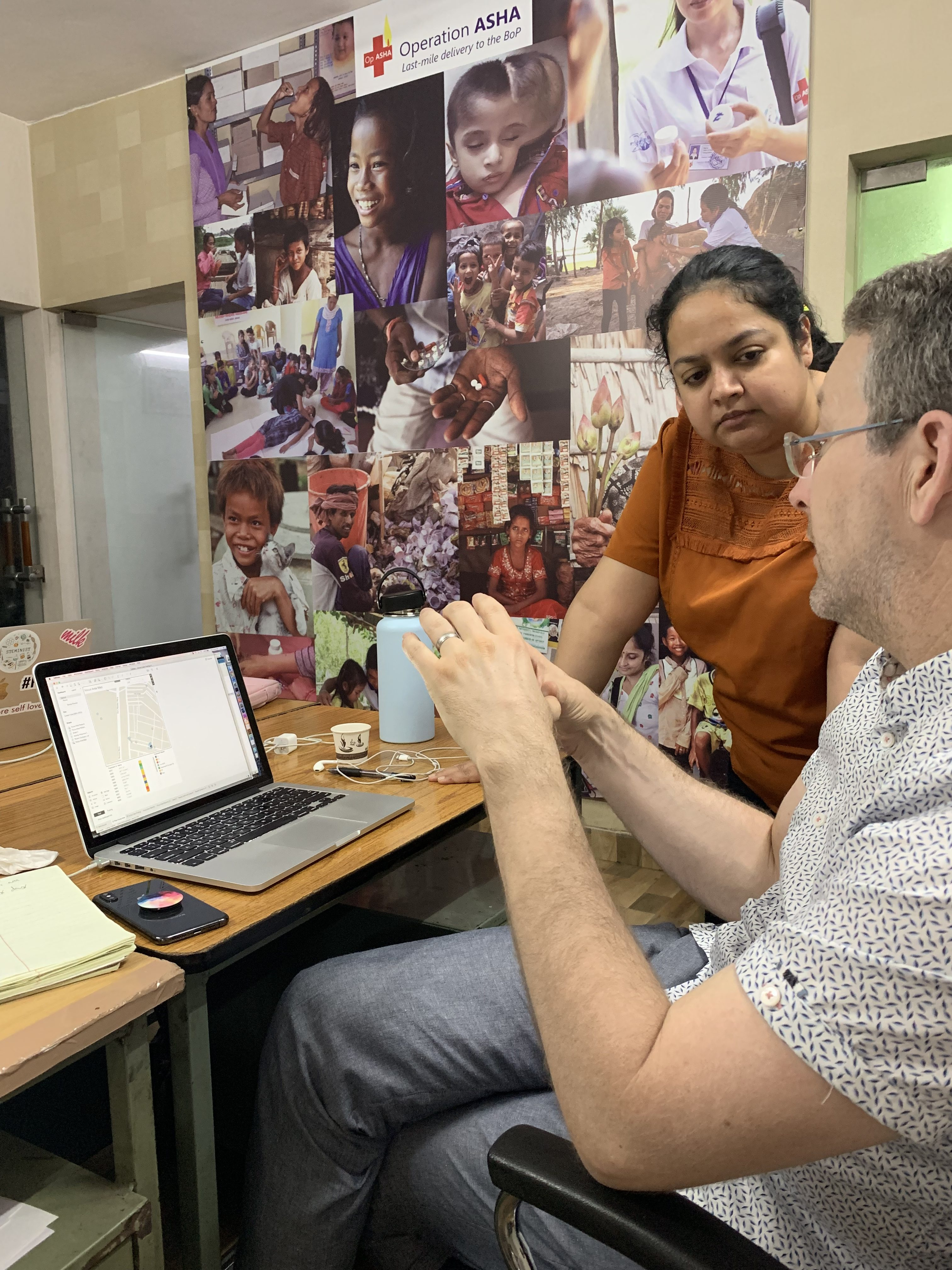 Tableau volunteer Michael and Operation ASHA staff looking at a computer discussing data modeling options