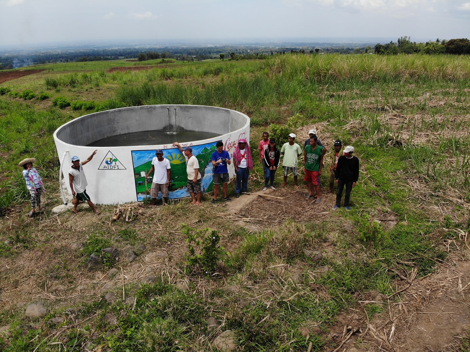 AIDFI team stands beside newly installed reservoir for Ram Pump to deliver water to village of Upper Atok