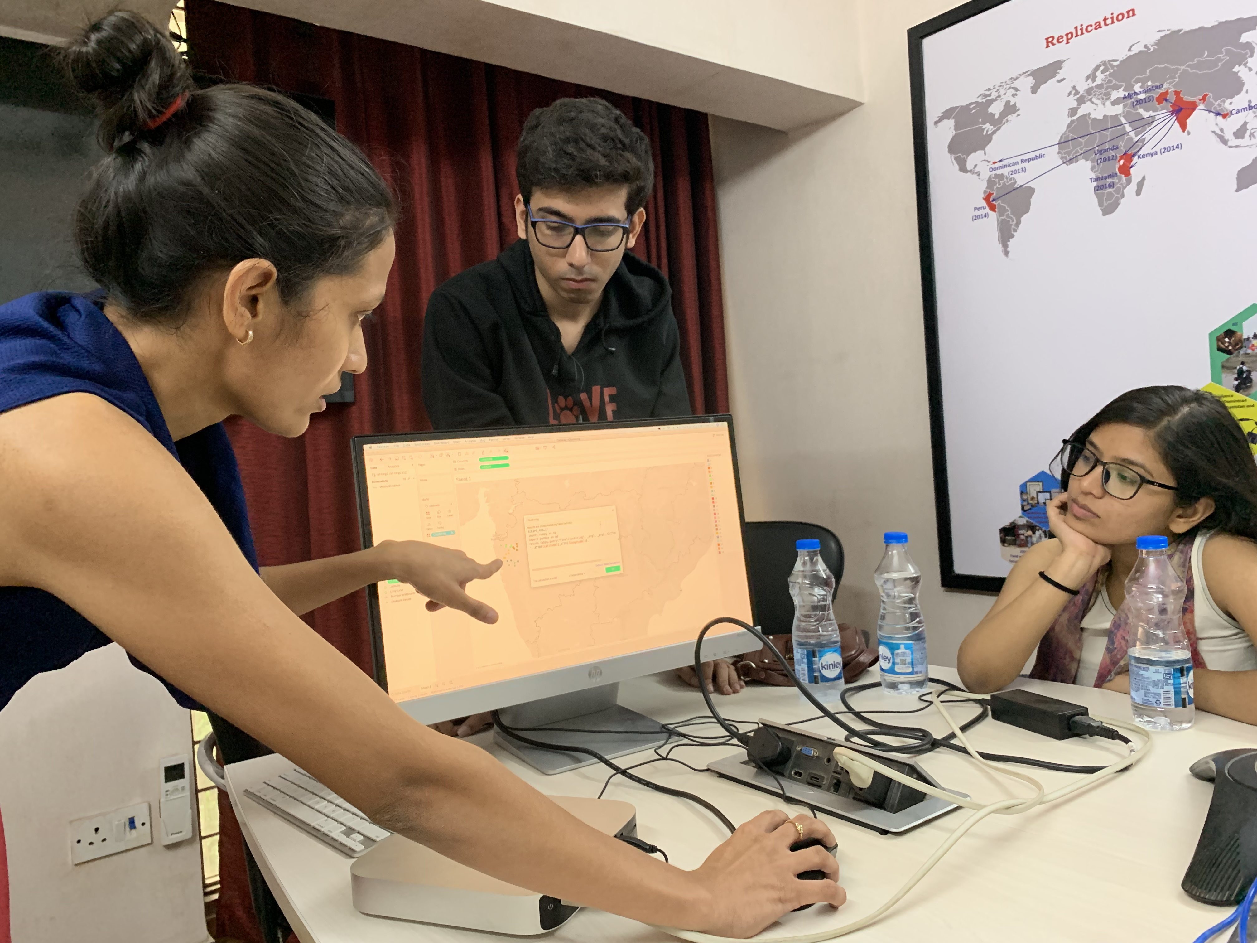 Operation ASHA staff pointing at a computer screen showing data clusters related to tracking TB in India