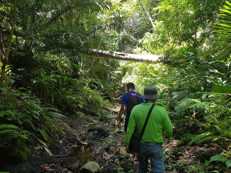 Skilled volunteer Stephen with AIDFI team member trekking to water source in Upper Atok Philippines