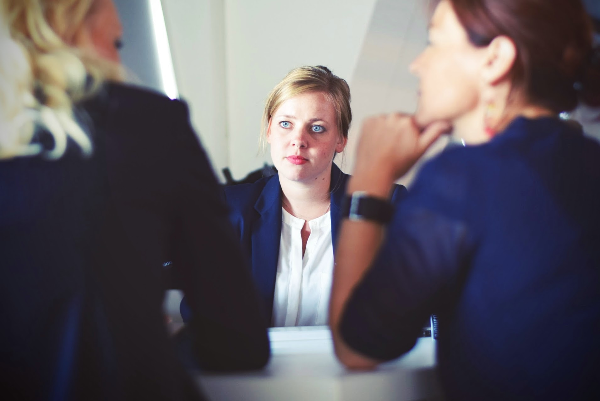 Woman in business suit sitting across the table from other businesswoman during an interview