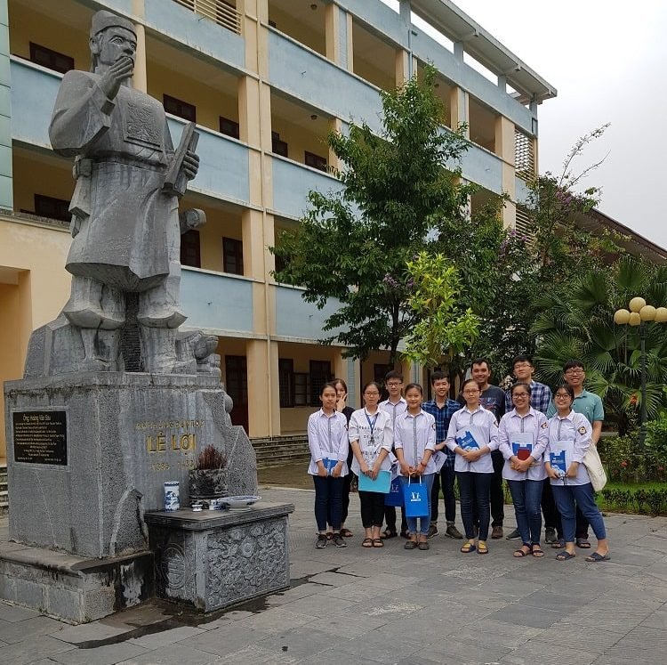 HOCMAI students, staff, and volunteer Sam posing in front of a school in Vietnam