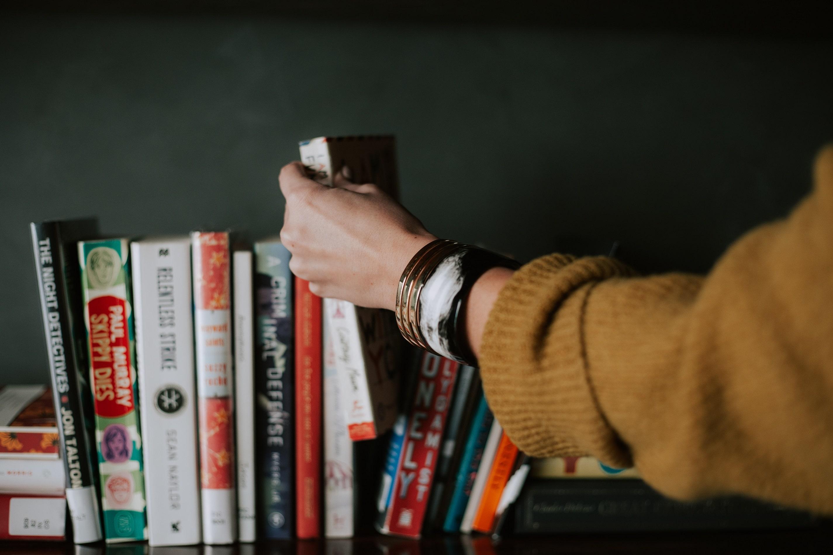hand taking book from bookshelf